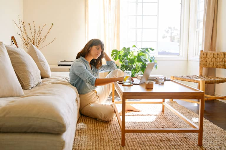 Woman sitting in her living room working on a laptop