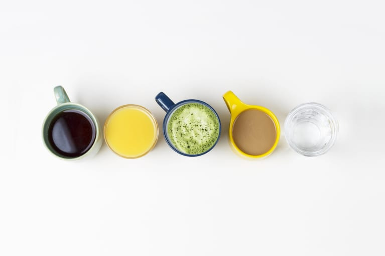 Coffee tea and other drinks in colorful cups on a white background, top view