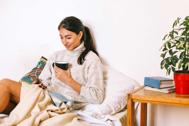 Woman Looking at Her Phone and Drinking Coffee on a Cozy Afternoon