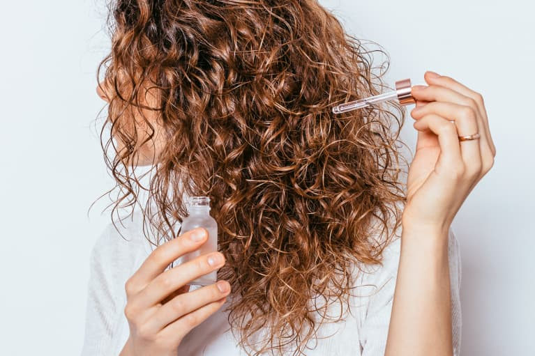 woman putting hair oil in hair