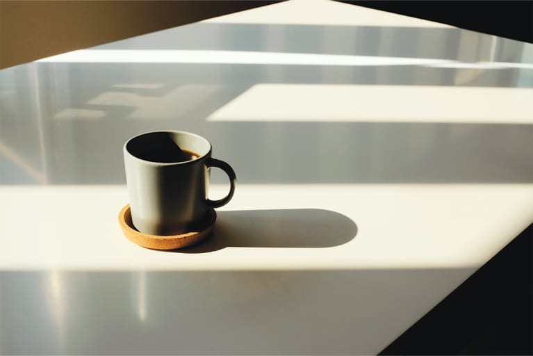White table with cup of coffee in a grey mug on a mustard-colored coaster