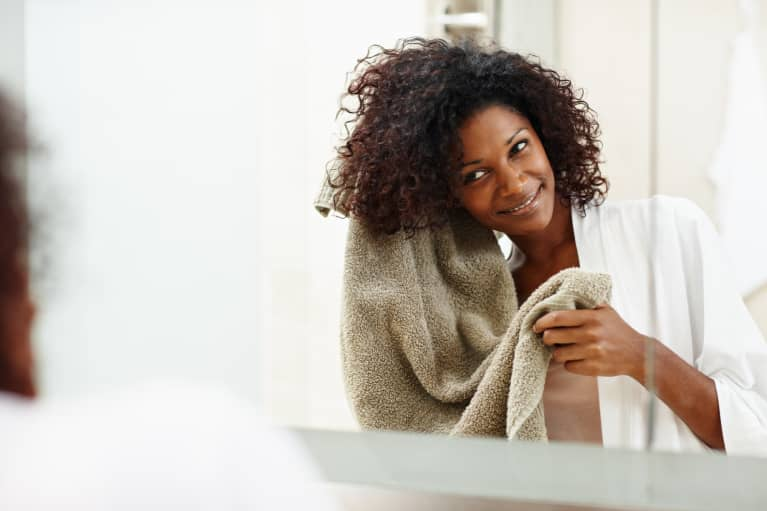woman drying her hair with a towel in the mirror
