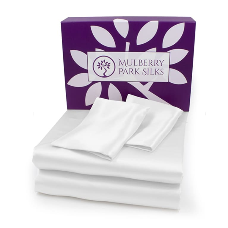 white silk sheets folded in front of purple box