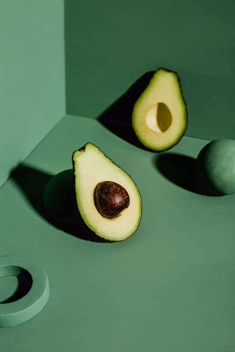 Abstract minimal still life of avocado on green background