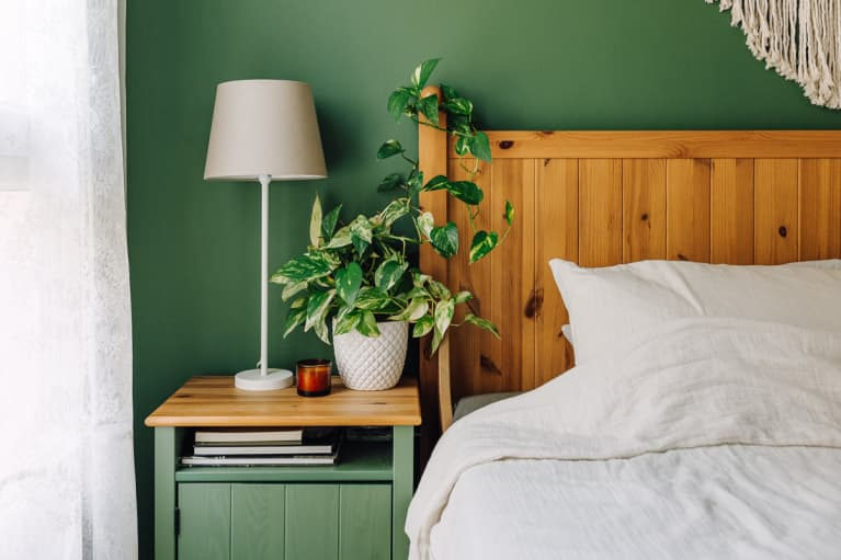 Sunlit Bed and Nightstand Against A Green Wall