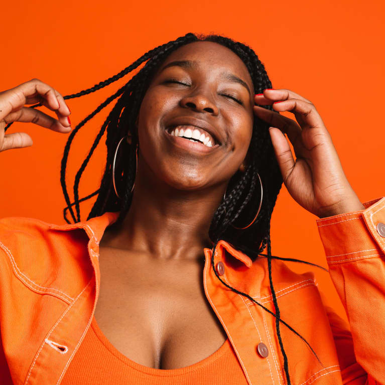 Young Woman Wearing Orange and Smiling Widely
