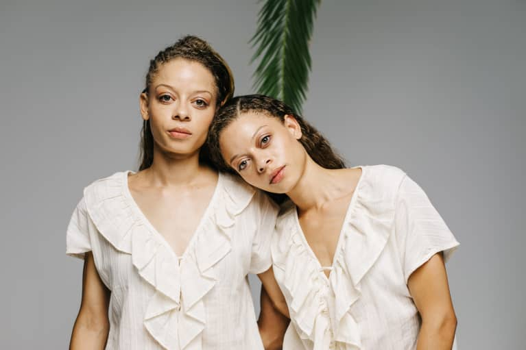 Twins in an embrace on grey background