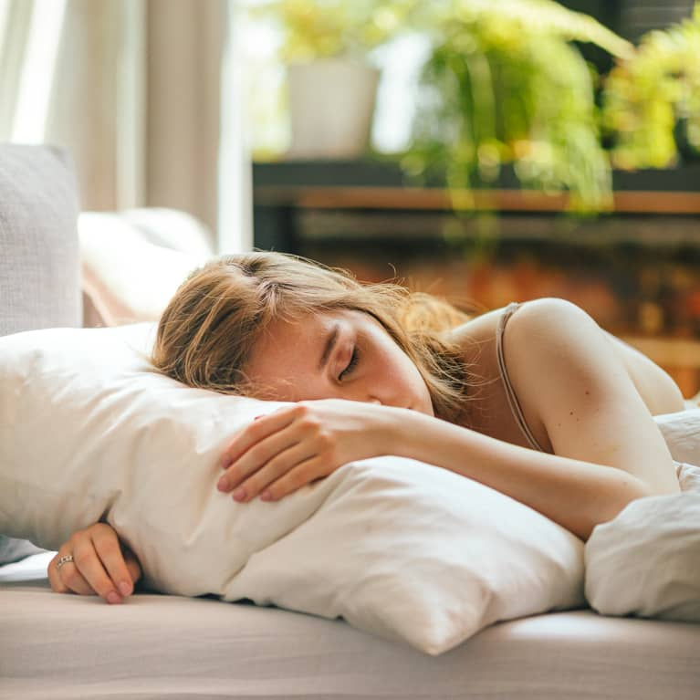 Young Woman Asleep in Bed on Sunny Morning
