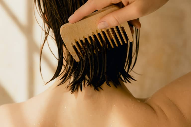 Woman brushing her hair with a wood comb