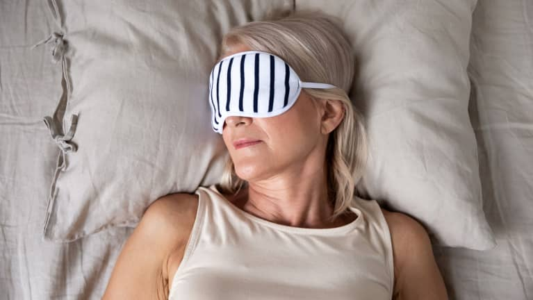 sleeping older woman with a mask on