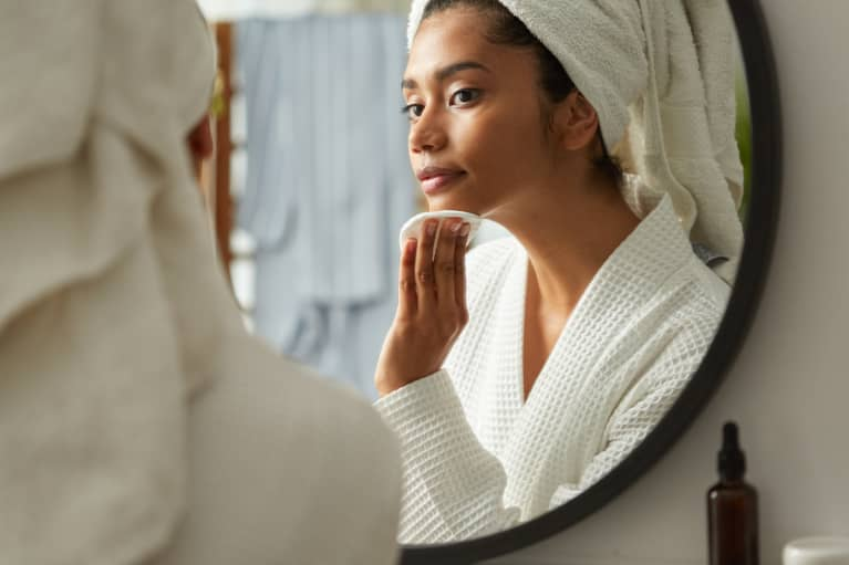 Woman in bathroom removing her make up while looking at the mirror in skincare morning routine at home
