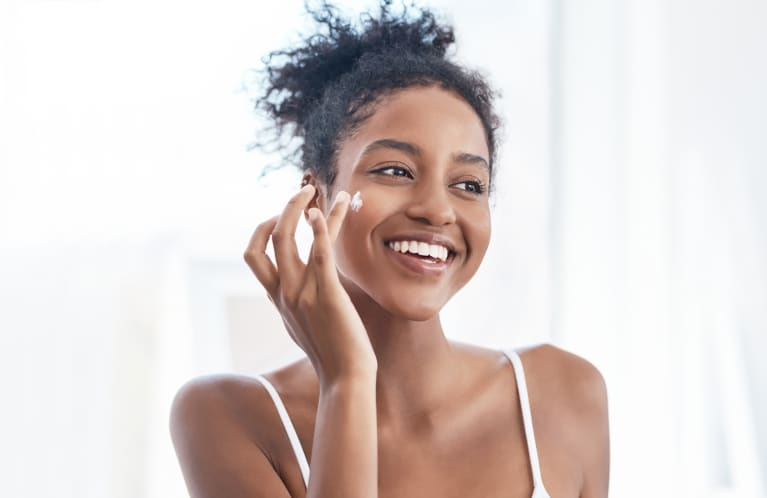 woman applying a face cream and smiling