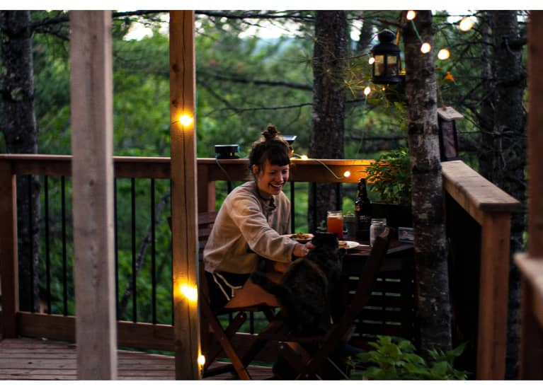 woman and cat eating dinner on porch of remote cabin
