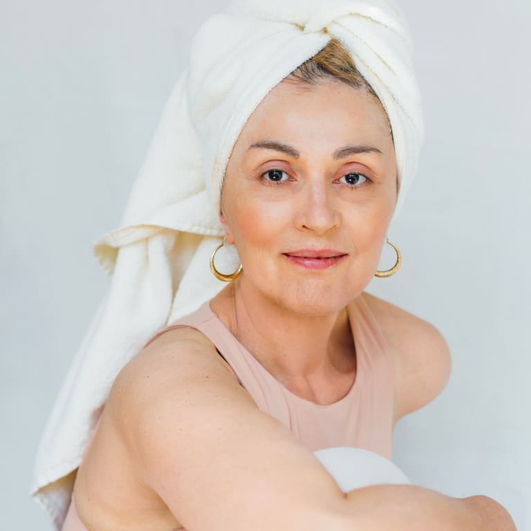 Portrait of a beautiful woman in her 60s with a towel on her head, looking at camera