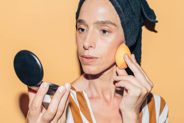 Close up of a beautiful middle aged woman using beauty sponge in front of an orange background