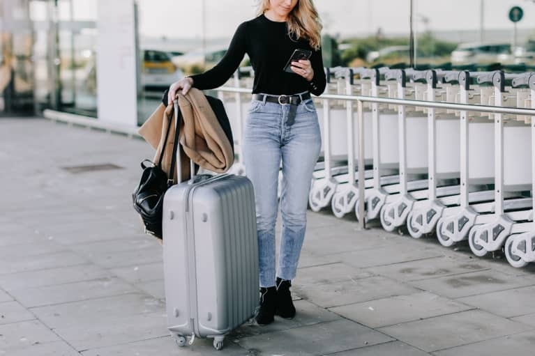 Image of woman traveling for work with a suitcase.