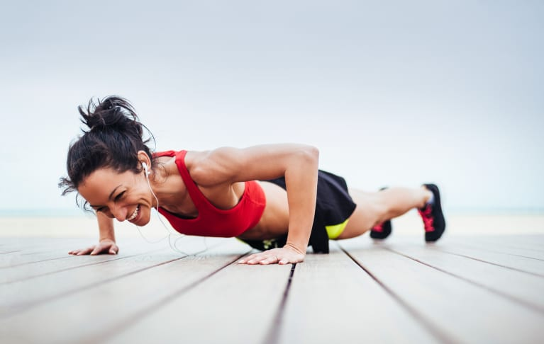 stock image of woman doing push up smiling