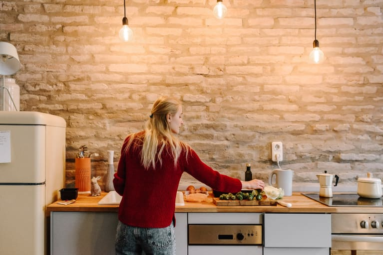 Image #2195144  Uploaded September 22, 2018 8:31 PM  Camera: NIKON D810  RELEASES Has 1 model release  Woman Cooking At Counter In Cozy Kitchen  Back view of young blond woman cooking dinner with vegetables at counter in trendy kitchen with brick wall