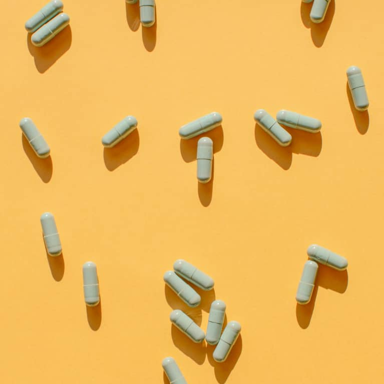 Overhead View of Probiotic Pills on a Yellow Background