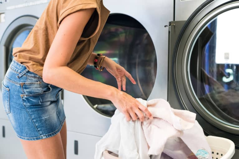 Woman loading clothes and athleisure into a clothes dryer