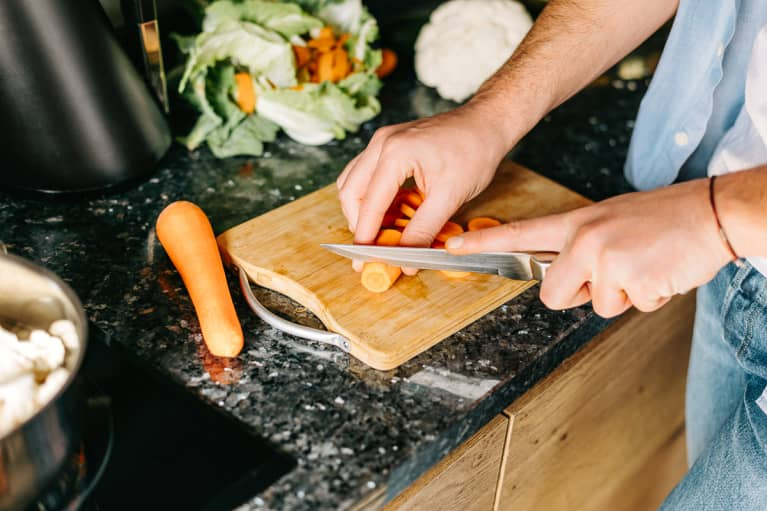 Man Chopping Carrots on a Counter