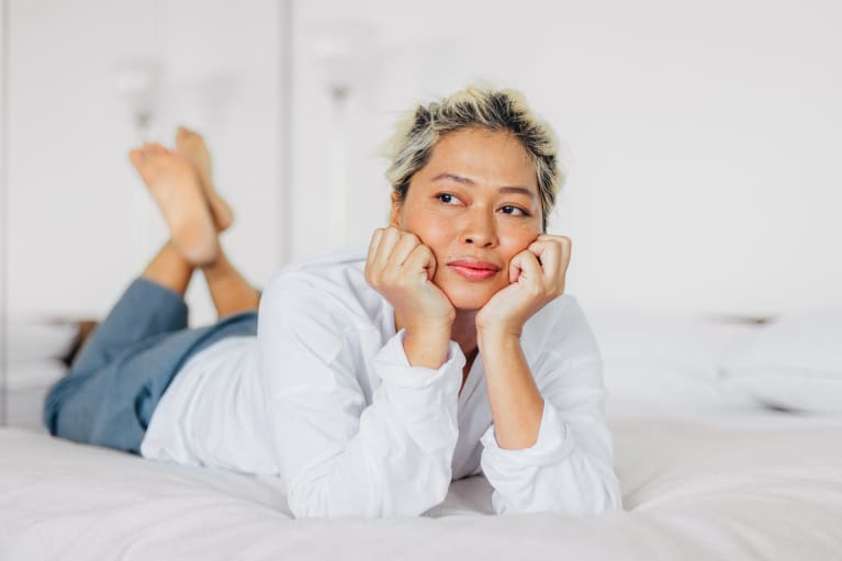 Woman in her 40s relaxing on her bed