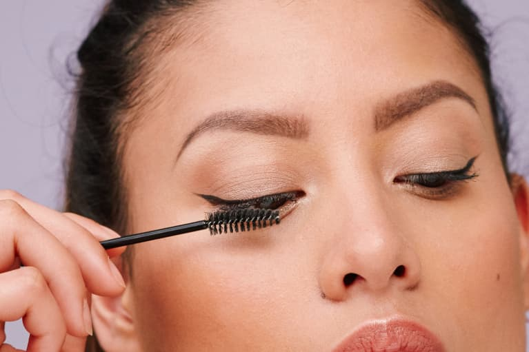 Woman Applying Mascara to Eyelashes