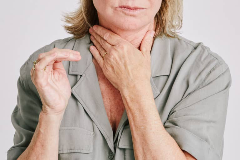 Woman With Her Hand on Her Throat Struggling with Shortness of Breath