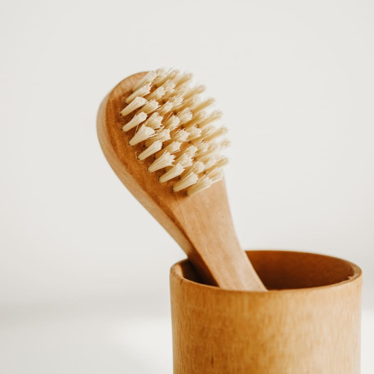 dry face brush in a holder on a white background