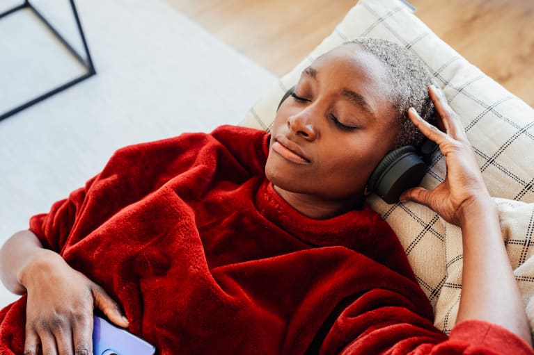 Woman Resting on the Couch Listening to Music