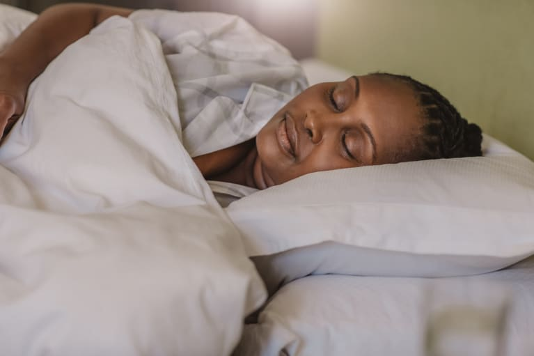 African American woman sleeping soundly in her bed at home stock photo