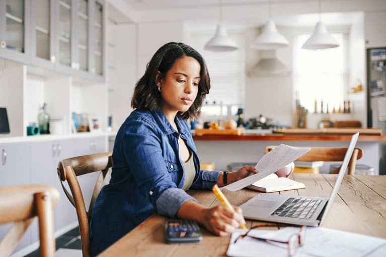 Woman Reviewing Her Finances At the Kitchen Table