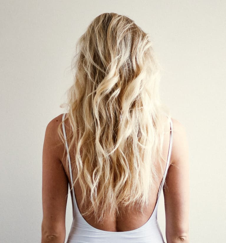 The back of a girl with long blonde wavy hair