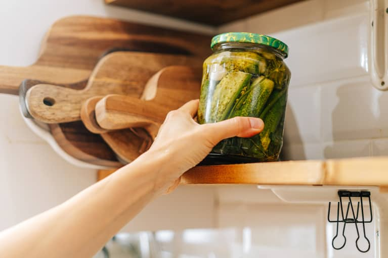 Hand Reaching For a Jar of Pickles on a Kitchen Shelf
