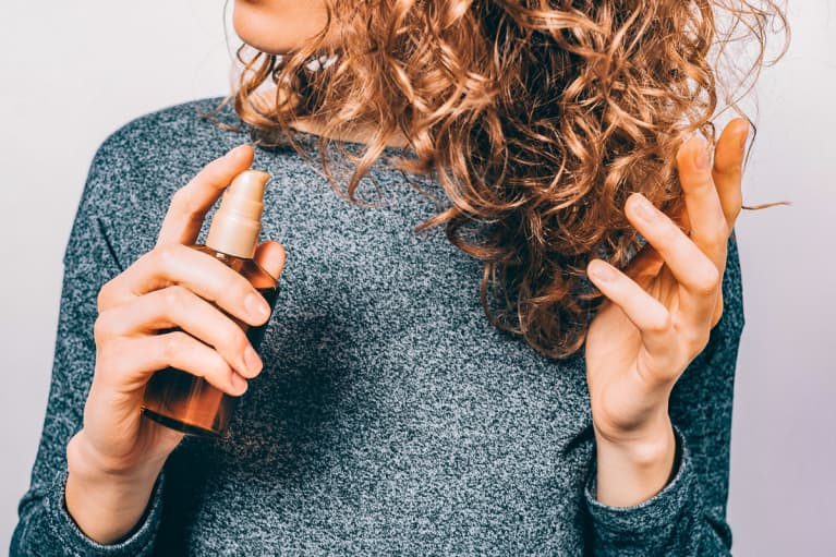 Woman Spraying a Serum into Her Hair