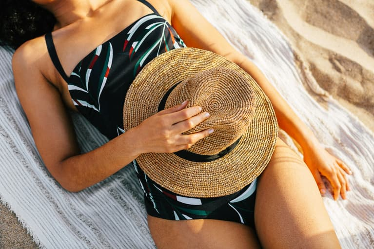 Woman Resting on the Beach with a Hat on Her Stomach