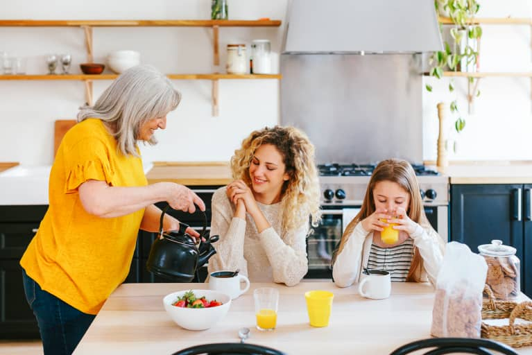 Grandmother, mother and daughter having breakfast on morning