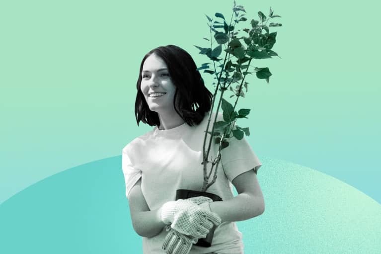 woman volunteering holding a plant looking happy