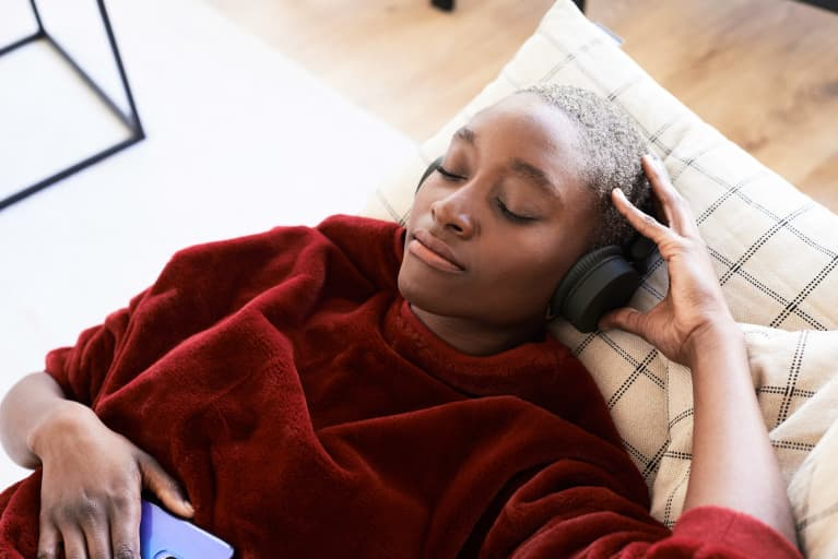 Woman reclined on couch listening to headphones