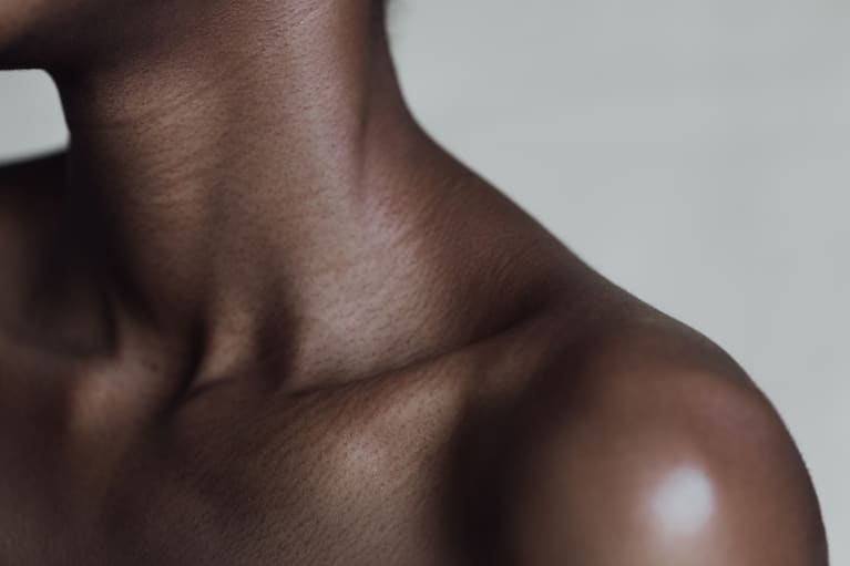 Close up shot of a woman's neck, collarbone, and shoulder