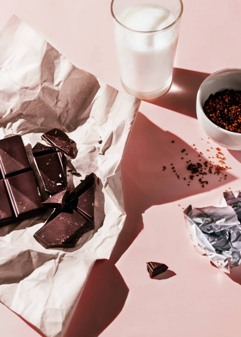 Side view of still life of chocolate bar, almond milk, and wrapper on pink seamless with strong lighting and shadows