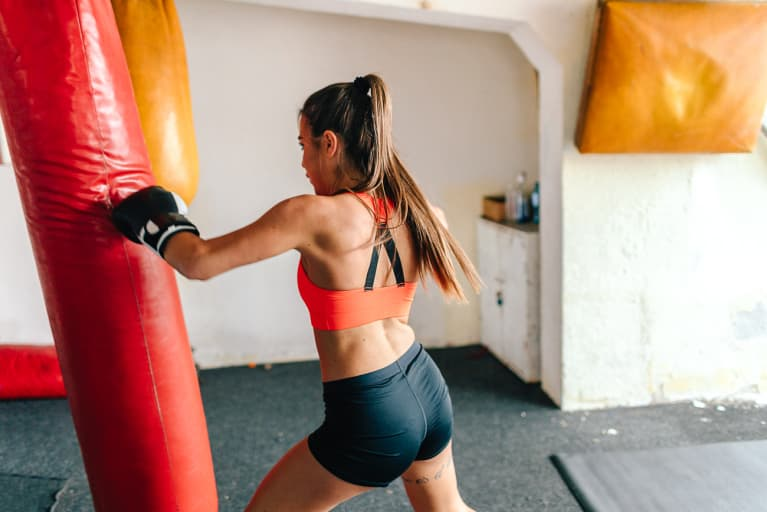 Woman Kickboxing and Punching a Weighted Bag