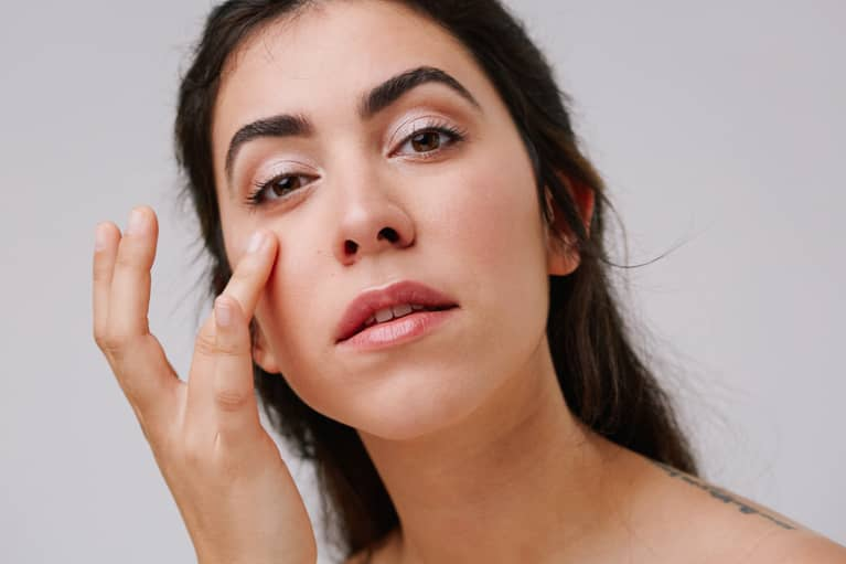 Young Woman Applying Eye Cream to Undereye