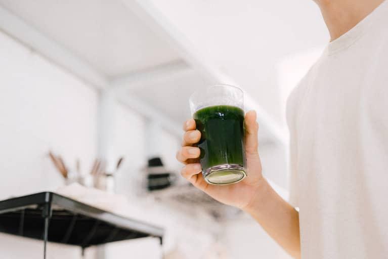 Man Holding a Glass of Dark Green Juice