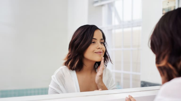 Young woman examining acne scars in mirror during her beauty routine