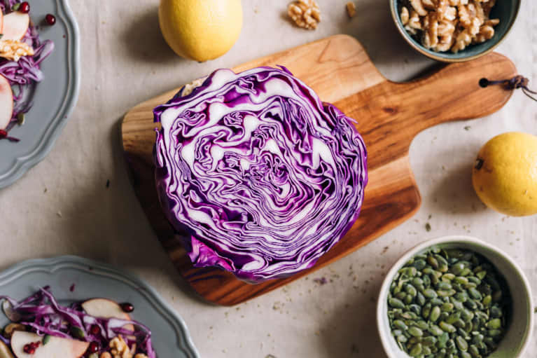 Overhead of sliced red cabbage on wooden cutting board with lemon, pepitas / pumpkin seeds, and walnuts