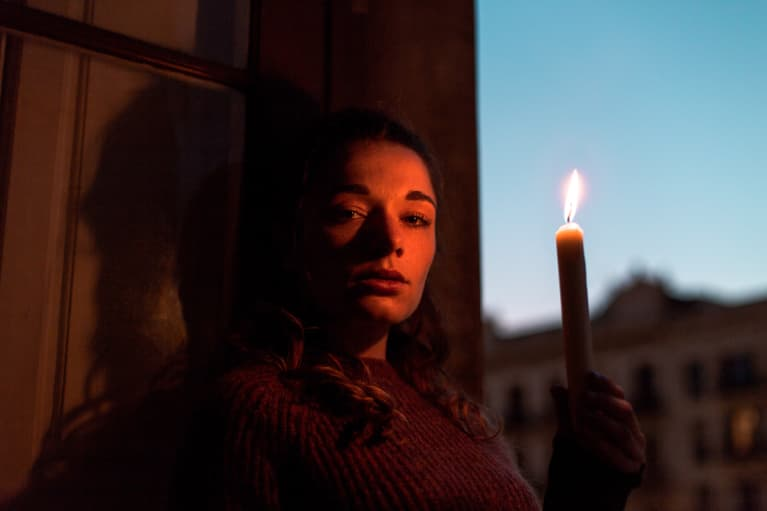 Portrait of a woman holding a candle light during sunset hour