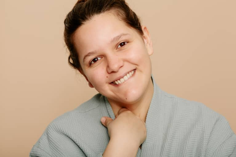 Woman smiling on a tan background