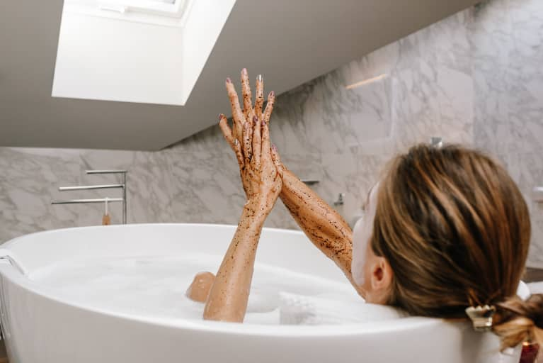 Woman in a Bath Tub Using a Body Scrub on Her Arms