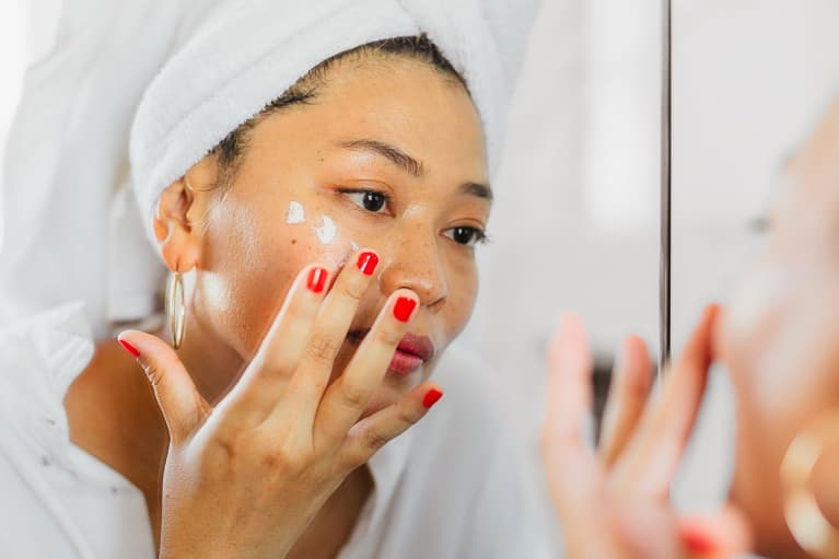Woman in Her 40s Applying Moisturizer in the Mirror